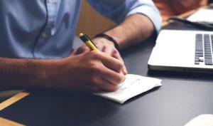 Lernender beim Online-Unterricht macht sich Notizen